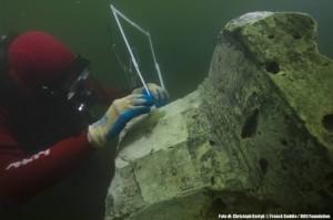 Un archeologo misura una colonna sottacqua